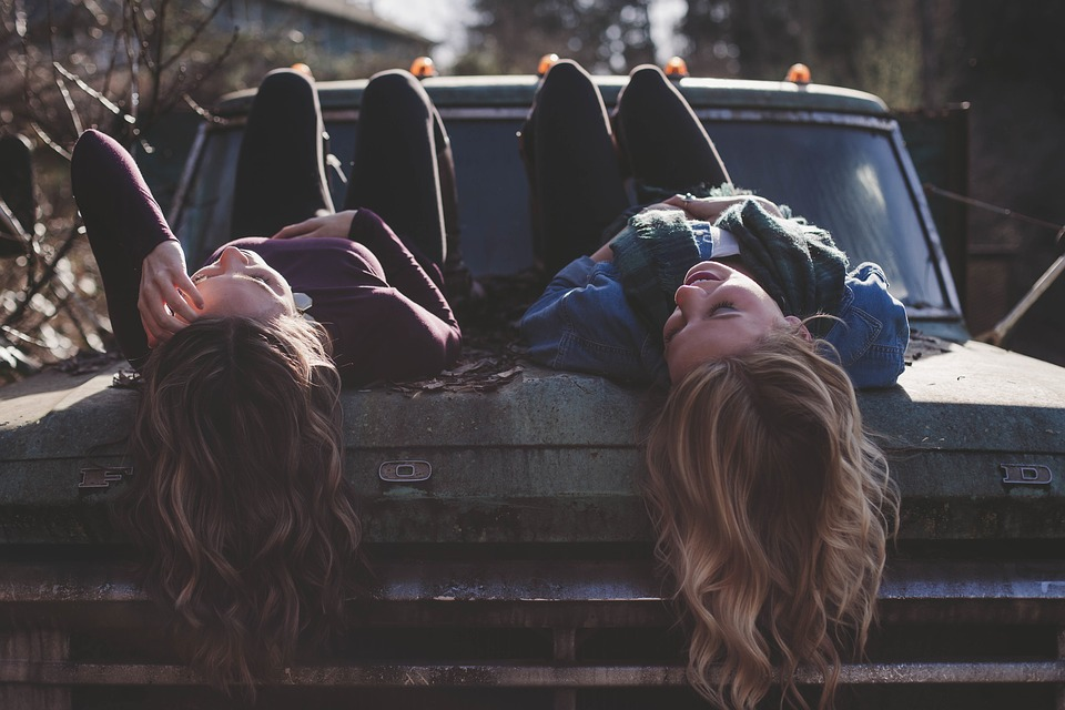 Two friends luying on a car.