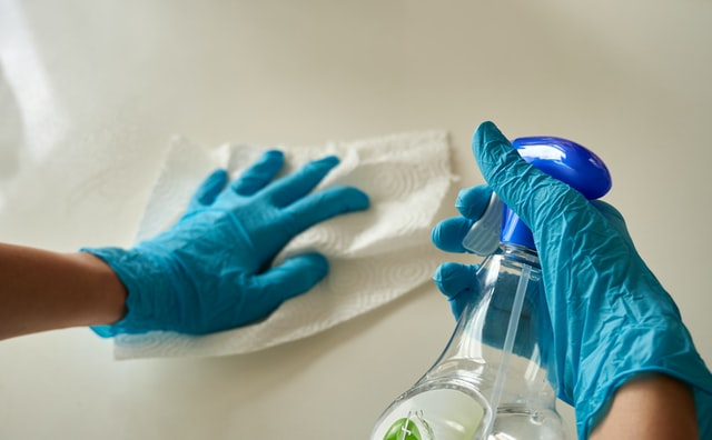 Hands with blue rubber gloves using cleaning products